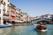 VENICE, ITALY - SEPTEMBER 24, 2019: Rialto Bridge, ancient buildings and motor boat floating on canal in Venice, Italy
