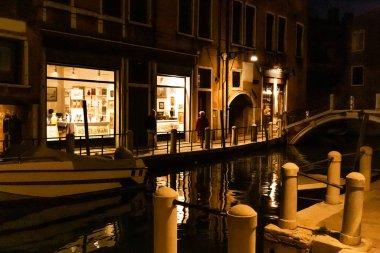 VENICE, ITALY - SEPTEMBER 24, 2019: motor boat near ancient building at night in Venice, Italy stock vector