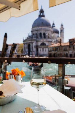 Selective focus of wine glass on table and Santa Maria della Salute church on background stock vector