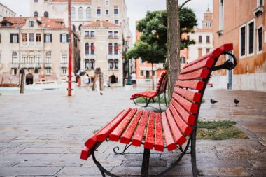 selective focus of red bench and ancient buildings on background in Venice, Italy