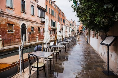 VENICE, ITALY - SEPTEMBER 24, 2019: outdoor cafe with view at canal and ancient buildings in Venice, Italy stock vector