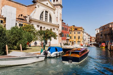 VENICE, ITALY - SEPTEMBER 24, 2019: vaporetto floating on canal near ancient buildings in Venice, Italy stock vector