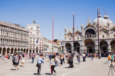 VENICE, ITALY - SEPTEMBER 24, 2019: tourists walking near Basilica of Saint Mark and clock tower in Venice, Italy stock vector