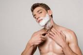 sexy muž s svalnatým trupem holení s rovnou břitvou izolované na šedé