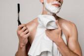 oříznutý pohled na sexy muže s svalnatým trupem a pěnou na holení na obličeji držící rovně břitvu a ručník izolované na šedé