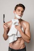 sexy muž s svalnatým trupem a pěnou na holení na obličeji drží rovnou břitvu a ručník izolované na šedé