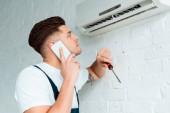 gutaussehender Installateur schaut auf Klimaanlage, während er mit Smartphone spricht und Schraubenzieher hält