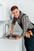 Fotografie glücklicher Installateur hält Kolben nahe Spüle in Küche