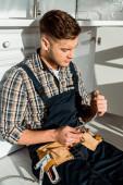 Fotografie schöner Installateur hält Metallschlauch in der Nähe von Küchenschrank