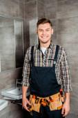 šťastný instalátor s nářadím pás stojící v koupelně