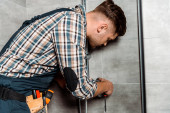 Photo serious installer in overalls standing in bathroom near pipe