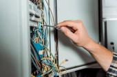 oříznutý pohled na elektrikáře držícího šroubovák poblíž rozvaděče