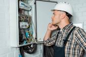 boční pohled zamyšleného elektrikáře dotýkajícího se obličeje při pohledu na ústřednu