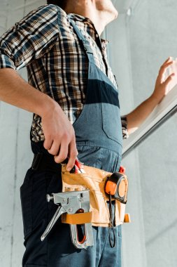 cropped view of installer in tool belt and overalls taking pliers