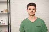 pohledný mladý muž v zeleném tričku s úsměvem na kameru, zatímco stojí v blízkosti stojanu s kosmetikou