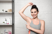 Photo joyful woman smiling at camera while applying deodorant on underarm