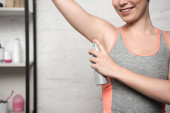 Photo cropped view of smiling woman in grey sleeveless shirt spraying deodorant on underarm