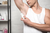 Photo partial view of young man in white sleeveless shirt applying deodorant on underarm