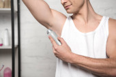 Photo cropped view of young man in white sleeveless shirt applying deodorant on underarm
