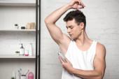 Photo young man in white sleeveless shirt spraying deodorant on underarm