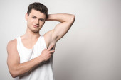 handsome man in white sleeveless shirt applying deodorant on underarm and smiling at camera on grey background