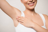 Photo partial view of smiling woman applying deodorant on underarm isolated on grey