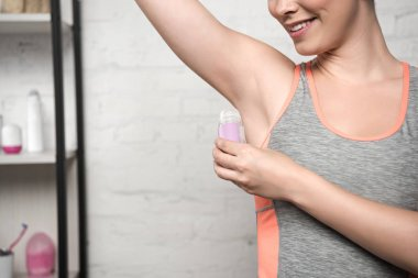 Cropped view of smiling woman applying deodorant on underarm stock vector