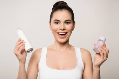 happy woman looking at camera while holding deodorants isolated on grey