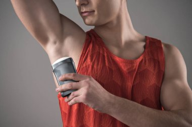 cropped view of young man in red sleeveless shirt applying deodorant on underarm isolated on grey