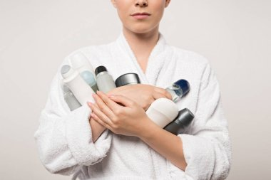partial view of woman in bathrobe holding different deodorants isolated on grey