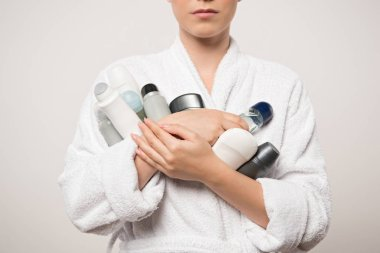 cropped view of woman in bathrobe holding different deodorants isolated on grey