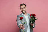 handsome positive man in suit holding red rose flowers, isolated on pink