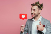 happy man in crown winking, showing thumb up and holding card with heart for valentines day, isolated on pink