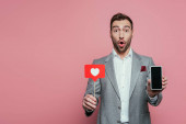 surprised man holding smartphone with blank screen and card with heart for valentines day, isolated on pink