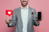cropped view of man holding smartphone with blank screen and card with heart for valentines day, isolated on pink