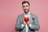 Fotografie happy man holding red heart for valentines day, isolated on pink