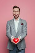 pohledný veselý muž drží červené srdce na Valentýna, izolované na růžové