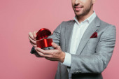 cropped view of man holding heart gift box for valentines day, isolated on pink