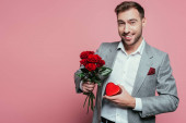 happy man holding heart gift box and bouquet of roses for valentines day, isolated on pink