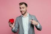 boldog szakállas férfi mutató szív ajándék doboz Valentin nap, elszigetelt rózsaszín