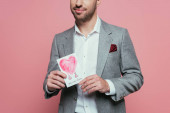 cropped view of man holding valentines day card with heart, isolated on pink