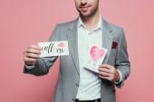 levágott kilátás férfi kezében két Valentin napi kártyák, elszigetelt rózsaszín