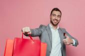 mosolygós férfi gazdaság bevásárló táskák és mutatja hüvelykujját fel, elszigetelt rózsaszín