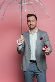 happy man holding proposal ring and umbrella, isolated on pink