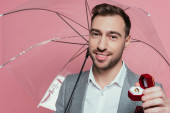 cheerful man holding proposal ring and umbrella, isolated on pink