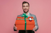 smiling man holding big present and proposal ring, isolated on pink