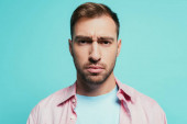 portrait of serious handsome man looking at camera, isolated on blue