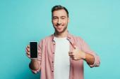 veselý muž ukazuje palec nahoru a smartphone s prázdnou obrazovkou, izolované na modré
