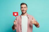 usmívající se muž ukazuje palec nahoru a drží kartu se srdcem na Valentýna, izolované na modré