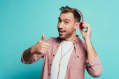 boldog ember zenét hallgat fejhallgatóval és mutatja hüvelykujját fel, elszigetelt kék